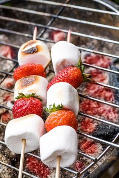 close up shut of marshmallows and stawberries on the grill